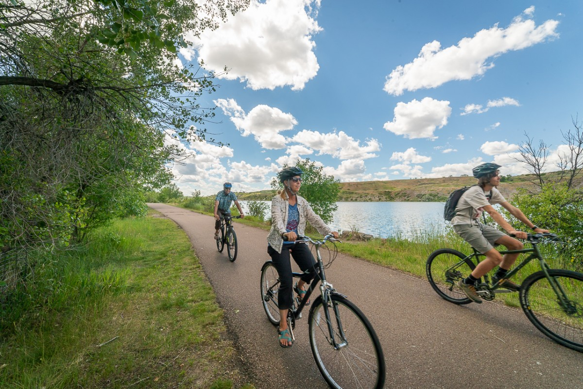 three people riding bikes in Giant Springs State Park along the Missouri River