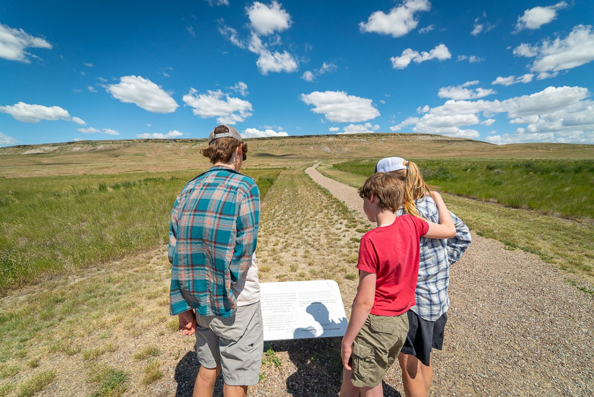 three people reading interpretive signs at a bison jump