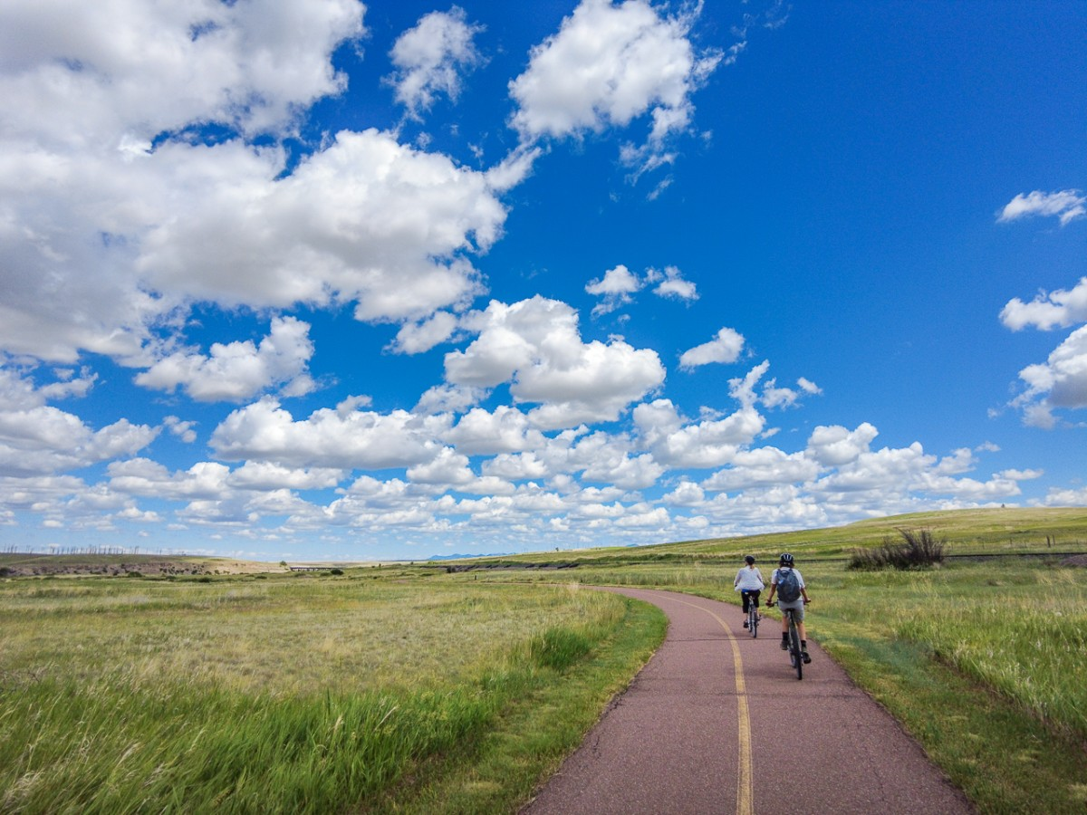paved bike path and two riders on the Great Falls bike trail Montana