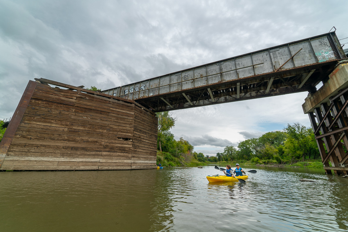 kayaking under a bridge on the red river in fargo