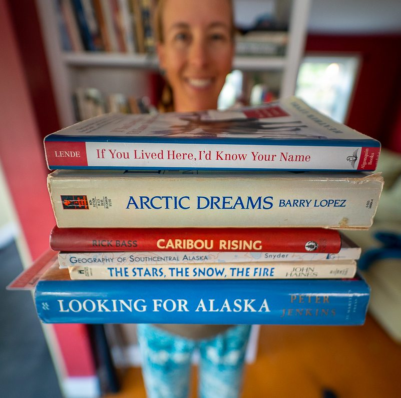 woman holding a stack of books set in Alaska