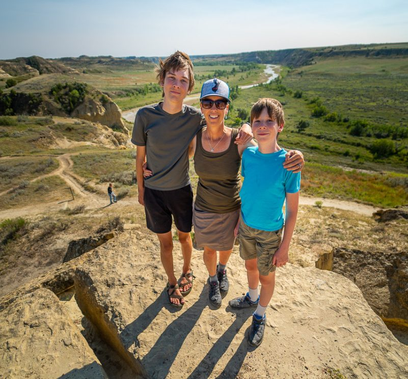 North Dakota tourist attractions include Theodore Roosevelt National Park where Travelingmel and her sons are standing
