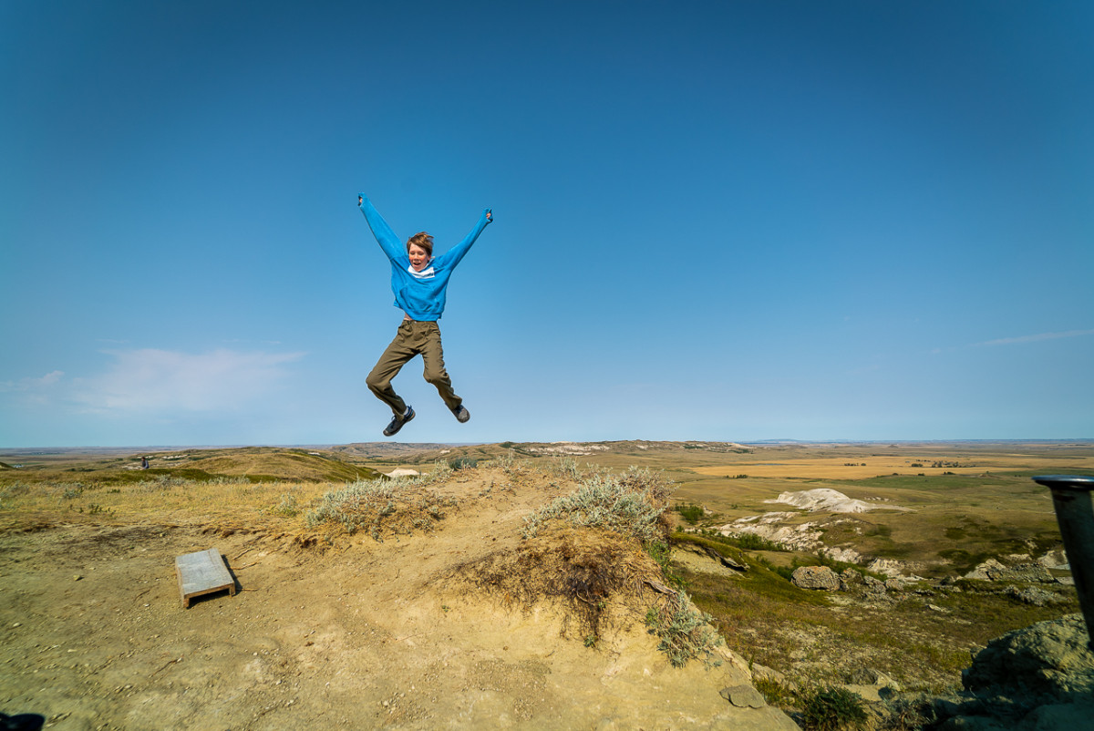 Kid jumping atop White Butte the highest point in North Dakota