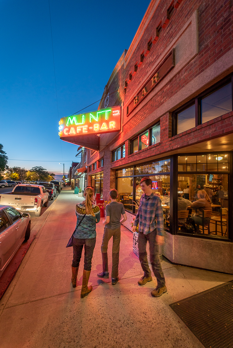 neon sign of the Mint Cafe and Bar in Belgrade mt with three people walking under it