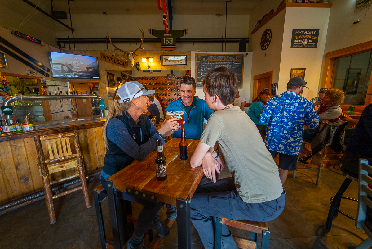 two people toasting a beer at Madison River Brewing Company in Belgrade MT